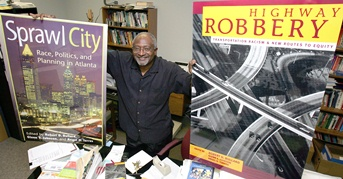 Robert Bullard standing with posters of several book covers